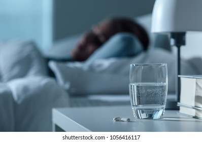 Woman sleeping in her bed at night, glass on water and pills on the foreground, medicine and treatment concept