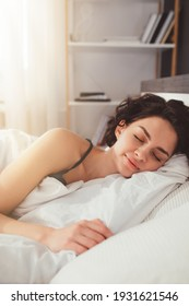 Woman sleeping. High angle view of beautiful young woman lying in bed and keeping eyes closed while covered with blanket. Stock photo