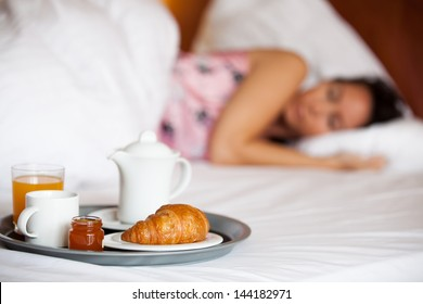 Woman is sleeping in a hotel with breakfast in front of her