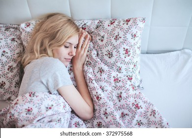 woman sleeping lying on the bed, covered with a blanket in the bedroom