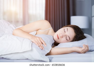 Woman sleeping on bed in the bedroom with soft light