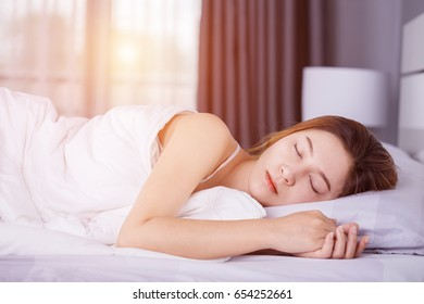 Woman sleeping on bed in bedroom with soft light