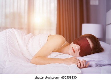 Woman sleeping on bed with eye mask in the bedroom with soft light