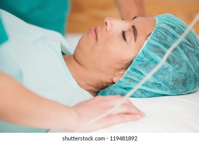 Woman sleeping on gurney before surgery in hospital corridor