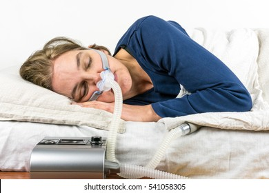 Woman sleeping on her side with CPAP machine in the foreground, sleep apnea treatment.
