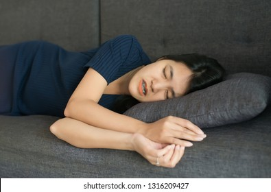 Woman sleeping on sofa and grinding teeth,Female tiredness and stress at home