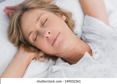 Woman sleeping peacefully in bed close up in bedroom at home
