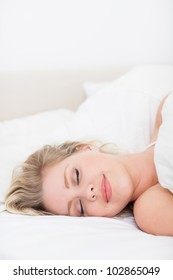 Woman sleeping with a smile in her bed