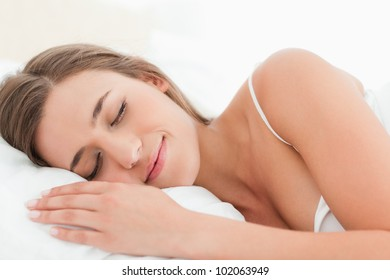 A woman sleeping and smiling softly in bed.