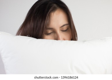 woman sleeping well in bed hugging soft white pillow