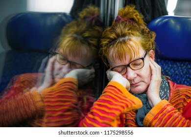 a woman sleeps exhausted during a train ride