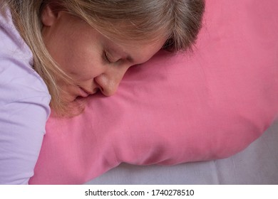 Woman sleeps on the stomach and embracing pillow. Close-up portrait of 40 years woman with calm and relax face sleeping on fresh bedclothes