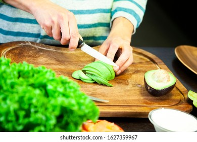 Woman slices an avocado on the wooden cutting board
