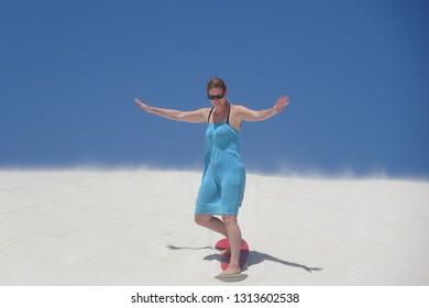 Woman sliding down a sand dune on a red sandboard in Lancelin Western Australia