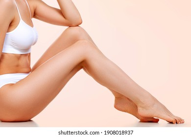 woman with slim beautiful body sitting against pastel background