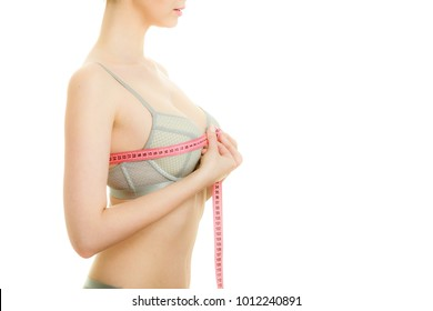 Woman slim girl in bra lingerie with red measure tape measuring her chest breasts. Closeup part of female body.