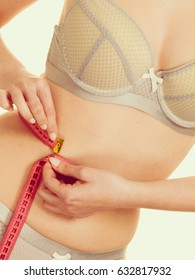 Woman slim girl in lingerie measuring her waist with measure tape. Time for diet slimming weight loss. Filtered photo