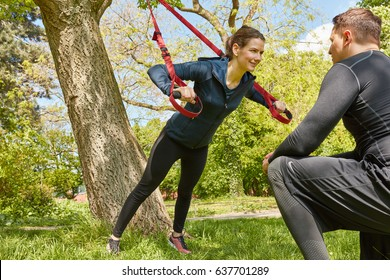 Woman sling training with Personal Trainer at park