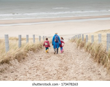 woman with small boy and girl in winter clothing and rubber boots walking down to a winter beach along a dune path