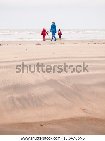 a0d968d2f1 woman with small boy and girl in winter clothing and rubber boots on a winter  beach