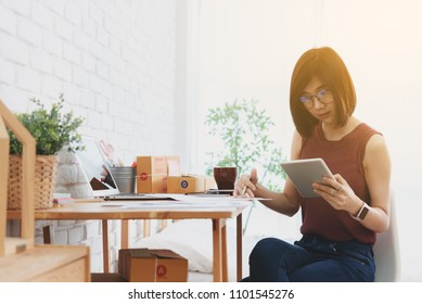 Woman small business owner, business start up conceptual, young entrepreneur work with paper report and tablet