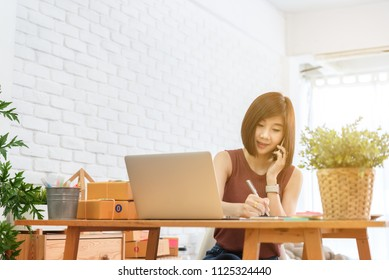 Woman small business owner, business start up conceptual, young entrepreneur work with laptop and smartphone take note