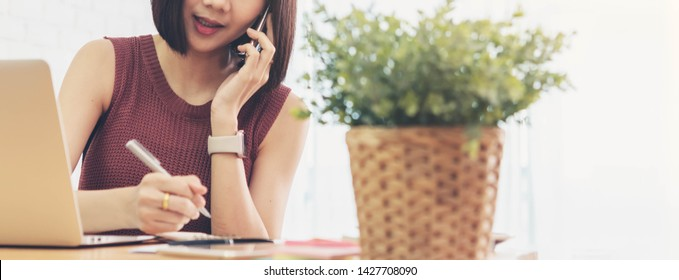 Woman small business owner, business start up conceptual, young entrepreneur work with laptop receiving phone call write down notes, banner wide dimension