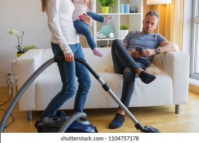Woman with small child doing housekeeping while man sitting in couch