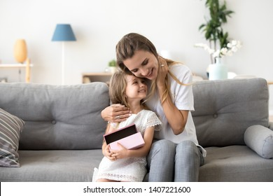 Woman and small preschool lovely girl sitting together on sofa at home. Happy cheerful mother hug little smiling daughter holding gift box. Happy motherhood or custody new mum for adopted kid concept
