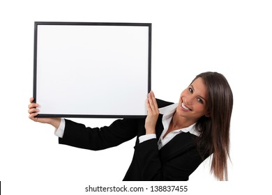 Woman in a smart black suit holding a board left blank for your image or message