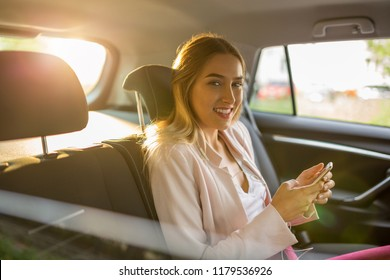 Woman with smart phone in a car
