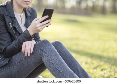 Woman with smart phone in spring park
