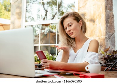 Woman with smart phone. Stunning cheerful elegant woman giving an air kiss during video call by cell phone, businesswoman freelancer sitting at the cafe and using a laptop.