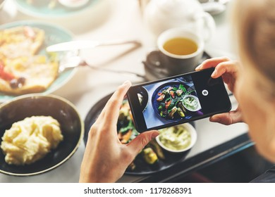 woman with smart phone taking picture of food at restaurant