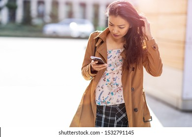 Woman with smartphone in downtown city street