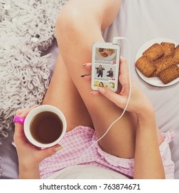 Woman with smartphone drinking coffee browsing social media in bed at home wearing pajamas