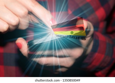 A woman with a smartphone, a German flag and a German word translation of a German language course
