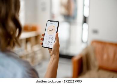 Frau mit Smartphone mit der Anwendung für die Anpassung der Lufttemperatur, Luftqualitätsüberwachung. Gesundheitsmikroklima zu Hause Konzept.