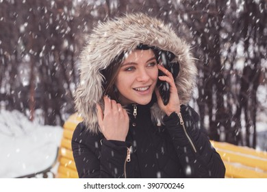 Woman with smartphone standing under showflakes in winter park