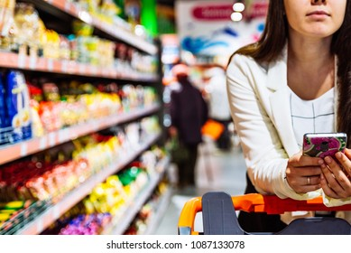 woman with smartphone in store. grocery shopping. gadgets and shopping.