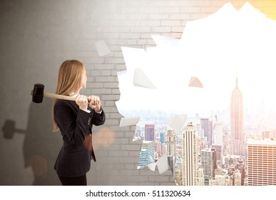 Woman is smashing wall with sledgehammer. Large city panorama is seen through the hole. Concept of finding your way in business. Toned image