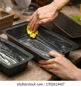 A woman smearing butter onto a baking pan before putting dough in. Bread making concept image.