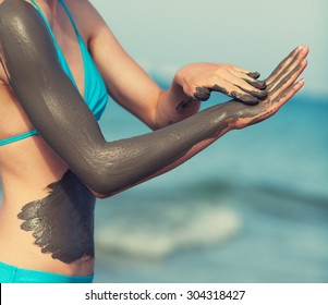 Woman smearing mud mask on the body