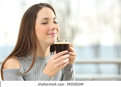 Woman smelling coffee aroma in a transparent cup in a terrace with the sea in the background