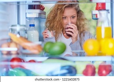 Woman smelling jam in front of fridge full of groceries. Picture taken from the iside of fridge.