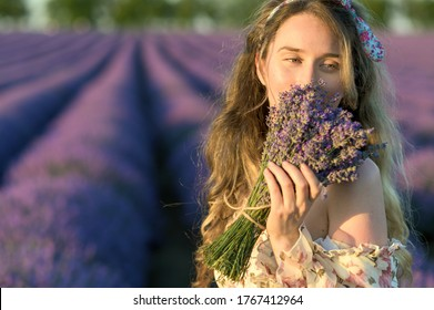 Woman smelling a lavender bouquet. Happy dreamy smile. Cute summer dress curly hair