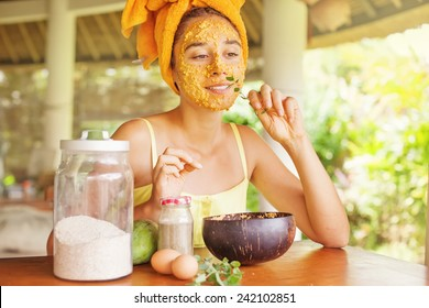 woman smelling a mint leave while doing face mask at home