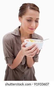 Woman smelling on her bowl of fruit salad against a white background