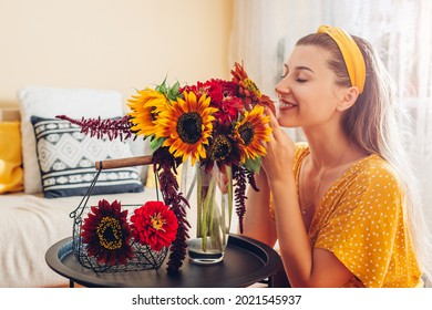 Woman smells bouquet of sunflowers with zinnia flowers arranging in vase at home. Lady enjoys fresh blooms. Interior