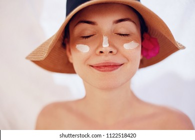 Woman smile applying sun cream  on face. Skincare. Body Sun protection. sunscreen. Female in hat smear  moisturizing lotion on skin.